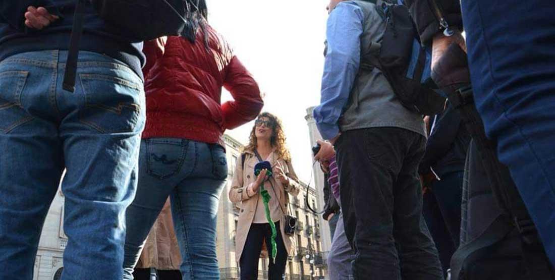 רנתה מדריכה סיור חינם בברצלונה, נתה עומדת ומסביב חבורה של אנשים שמקשיבים להסבר