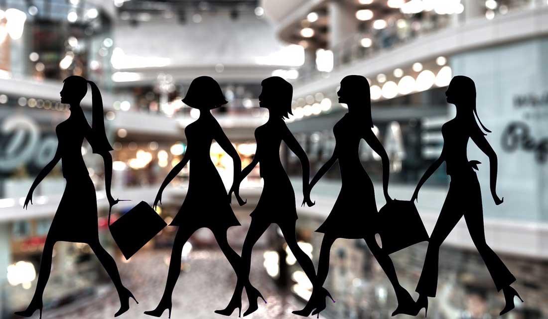 צלליות של נשים עורכות קניות על רקע קניון